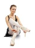Ballerina puts on pointe Stock Photography