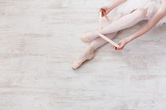 Ballerina puts on pointe ballet shoes, graceful legs. Ballet backgroung with copy space top view. Choreography and dancing classes concept. Beautiful legs of royalty free stock photos