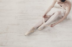 Ballerina puts on pointe ballet shoes, graceful legs. Beautiful legs of young ballerina who puts on pointe shoes at white wooden floor background, top view from Stock Images