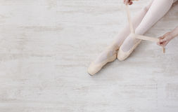 Ballerina puts on pointe ballet shoes, graceful legs Royalty Free Stock Photos