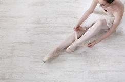 Ballerina puts on pointe ballet shoes, graceful legs Royalty Free Stock Images