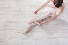 Ballerina puts on pointe ballet shoes, graceful legs Stock Photo