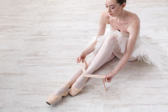 Ballerina puts on pointe ballet shoes, graceful legs Stock Photography