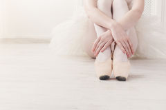 Ballerina puts on pointe ballet shoes, graceful legs Stock Images