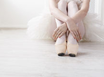 Ballerina puts on pointe ballet shoes, graceful legs. Closeup of young ballerina legs, sit in pointe shoes at white wooden floor background, with copy space Stock Photos