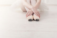 Ballerina puts on pointe ballet shoes, graceful legs. Ballet practice. Beautiful slim graceful feet of ballet dancer. Closeup of ballerina legs, sit in pointe Royalty Free Stock Photo