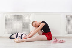 Ballerina puts on pointe ballet shoes,. Young tired ballerina in ballet studio, sit in pointe ballet shoes on floor stock image