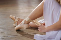 Ballerina putting on her ballet shoes