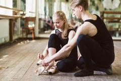 Ballerina putting on her ballet shoes royalty free stock images