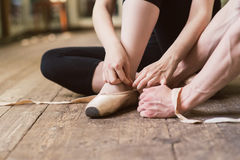 Ballerina putting on her ballet shoes royalty free stock photos