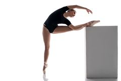 Ballerina putting her leg on cube while warming up Royalty Free Stock Images