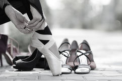 Ballerina Putting Pointe Ballet Shoes on her Feet. Closeup of a ballerinas feet in Pointe on the street, different kind of shoes in background stock photography