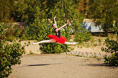 Ballerina in red tutu dancing in park. Grande pas des chat Stock Image