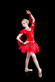 Ballerina in red tutu posing on black Stock Photos