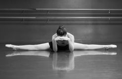 Ballerina Resting. Black & White photo of a ballerina stretching her middle splits, in the studio with barre background Royalty Free Stock Image