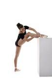 Ballerina satte hennes fot på kuben och bandpointes Arkivfoton