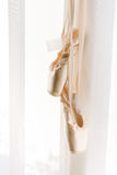 Ballerina shoes hanging. Hanging ballerina dancing shoes on a white wall background Stock Photo