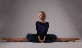 Ballerina show split on the studio floor. Ballerina in blue outfit posing , studio background Royalty Free Stock Images