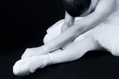 Ballerina sit down on floor to put on slippers Royalty Free Stock Image