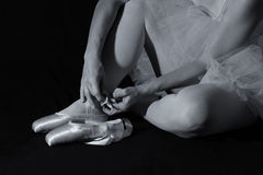 Ballerina sit down on floor to put on slippers Royalty Free Stock Photo