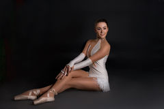 The ballerina sits and has a rest. The ballerina in pointes sits and has a rest Stock Image