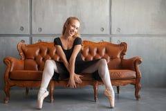 Ballerina sits on sofa royalty free stock photo