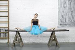 Ballerina sits on split in studio. Beautiful ballerina sits on the split on the long wooden table on the textured white wall background in the studio. She wears Royalty Free Stock Images