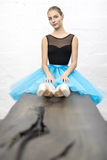 Ballerina sits on table. Attractive ballerina sits on the wooden table on the textured white wall background in the studio. She wears a black leotard with a cyan stock photography