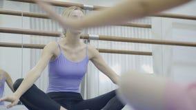 Ballerina sitter det lade benen på ryggen korset och shower hur man böjer från sidan med lyftta händer i balettgruppen stock video