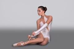Ballerina sitter och binder pointes royaltyfria foton