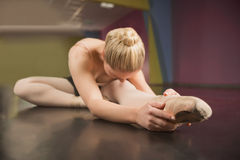 Ballerina sitting and bending forward Stock Photography