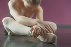 Ballerina sitting and bending forward. In the ballet studio stock photo