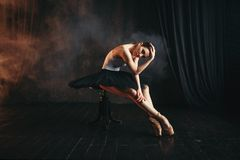 Ballerina sitting on black banquette in theatre. Ballerina sitting on black banquette on the stage in theatre. Elegance ballet dancer poses in class stock image