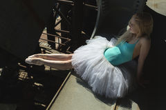 Ballerina sitting on the edge of bridge Stock Image