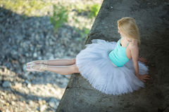 Ballerina sitting on the edge of bridge Royalty Free Stock Image
