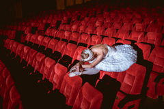 Ballerina sitting in the empty auditorium theater Royalty Free Stock Image