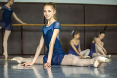 Ballerina sitting on the floor in the splits in a dance class da. Ncers practicing on the background. Dancer is smiling Stock Photo
