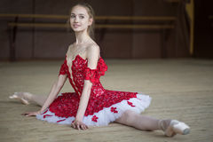 Ballerina sitting on the floor in the splits dressing in red tut Royalty Free Stock Images