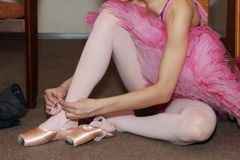 Ballerina tying Pointe shoes. Ballerina sitting on the floor tying Pointe shoes stock photography