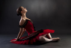 Ballerina sitting over black background Stock Images