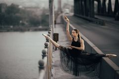 Ballerina sitting in twine pose on the bridge through the river. Ballerina sitting in twine pose in a black transparent dress on the bridge through the river royalty free stock images