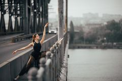 Ballerina sitting in twine pose on the bridge through the river. Ballerina sitting in twine pose in a black transparent dress on the bridge through the river royalty free stock photography