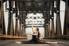 Ballerina sitting in twine pose on the road and rails next to metal supports
