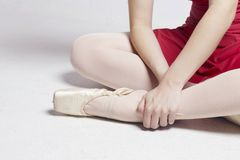 Ballerina sitting on a white floor, touching her foot. Ballerina sitting on a white floor, touching her foot, suffering pain on her fingers and ankle. No pain Stock Photography