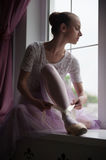 Ballerina sitting on windowsill. Closeup portrait of young and beautiful modern style ballet dancer sitting on window sill, tying up ballet shoes Royalty Free Stock Photography