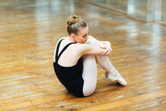 Ballerina sitting on the wooden floor Stock Images