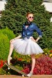 Ballerina skateboarding. Listen to music. Stock Photos