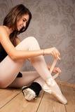 Ballerina som binder hennes baletthäftklammermatare royaltyfri foto