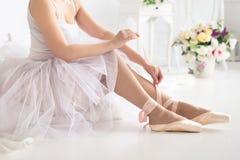 Ballerina som binder pointebalettskor close upp arkivfoto