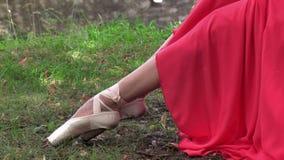 Ballerina som binder pointeskor som sitter yttersidan arkivfilmer